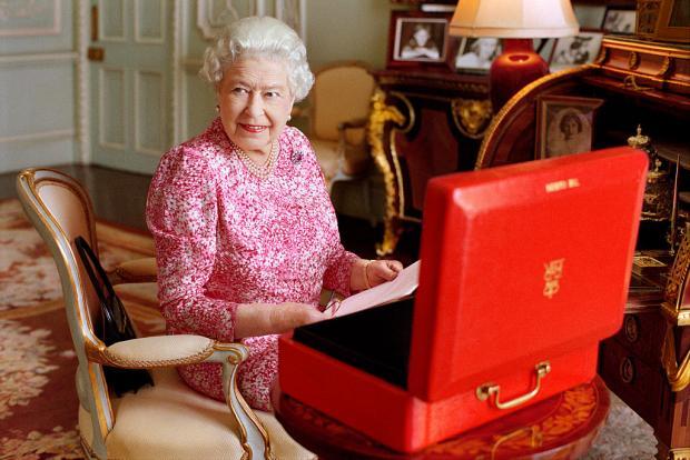 Елизавета II сидит за столом перед красным чемоданчиком