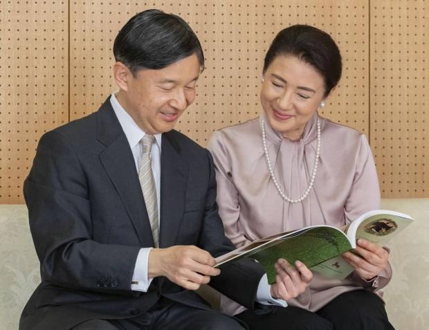 Император и императрица Японии рассматривают журнал