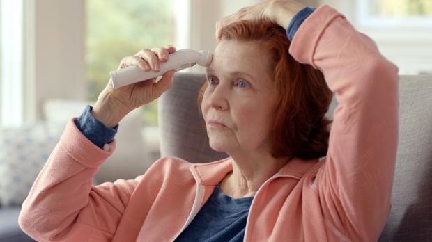 пожилая женщина меряет температуру