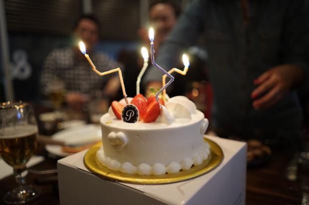на столе стоил красивый белый торт с зажженными свечками