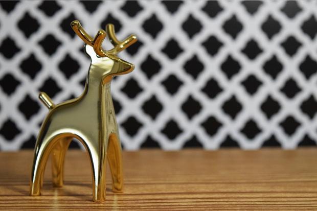 фигурка золотого оленя на фоне белой решетки