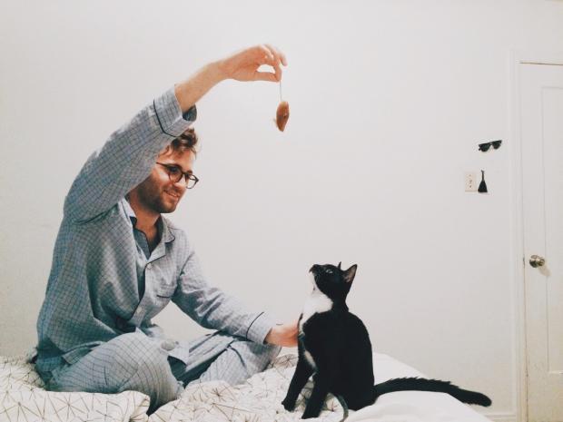 мужчина в пижаме играет на постели с котом