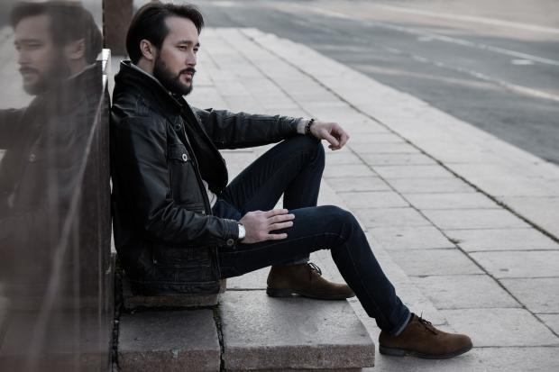 молодой человек сидит на тротуаре
