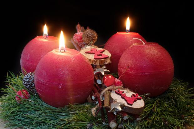 круглые красные свечи горят на рождественском венке