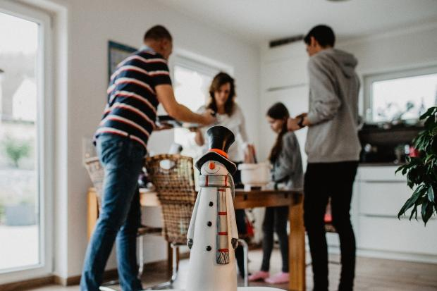 семья накрывает стол, снеговик на переднем плане