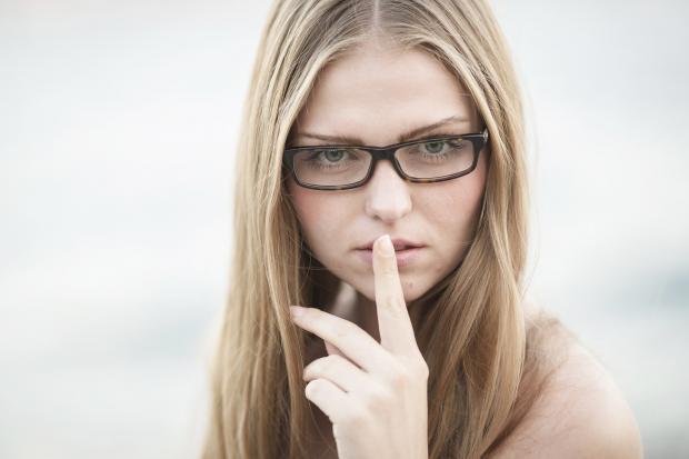 девушка в очках держит палец у рта