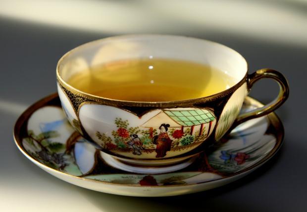 зеленый чай в красивой чашке с блюдцем