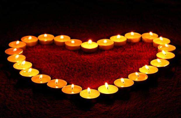 горящие свечи в форме сердца на красном фоне