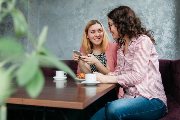 две девушки общаются в кафе
