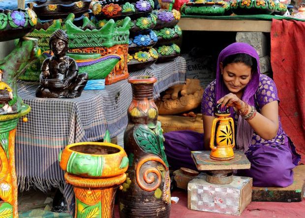 женщина продает продукцию гончарной мастерской в Индии