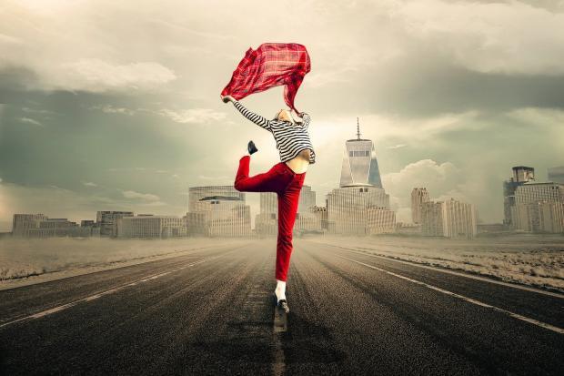 девушка в красных брюках и с красным шарфом танцует на фоне городского пейзажа
