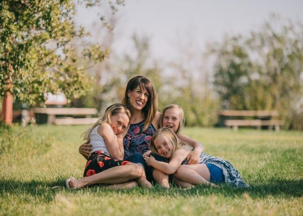 мама с тремя дочками сидят в обнимку на траве в парке