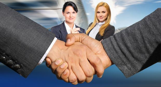 мужское рукопожатие на фоне двух девушек - переговоры
