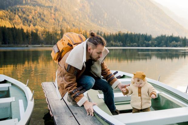 Молодой мужчина в теплой одежде и маленький ребенок в лодке