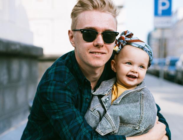 Молодой мужчина в солнцезащитных очках обнимает маленького ребенка
