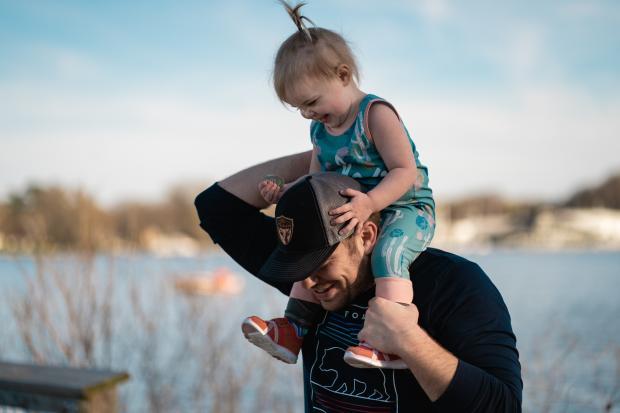 Мужчина в темной кофте и бейсболке держит на плечах ребенка