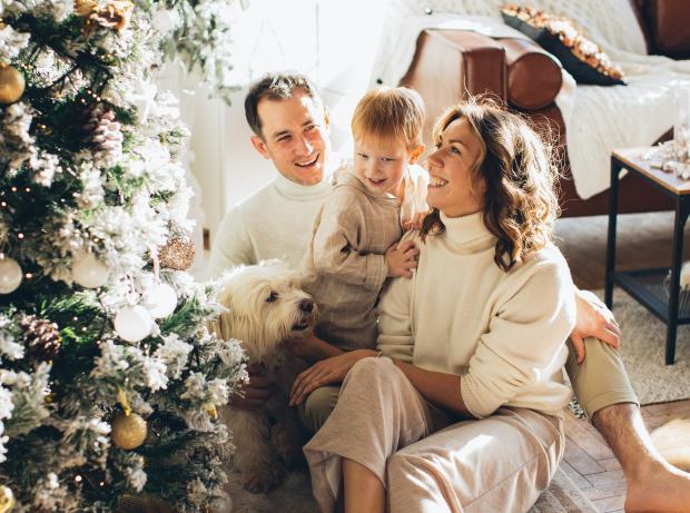 Семья с домашним питомцем возле новогодней елки