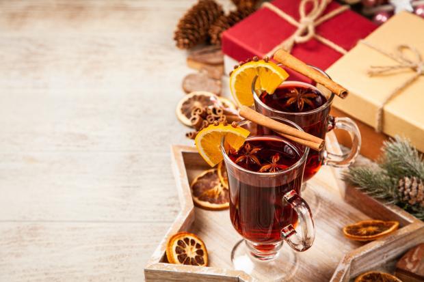 Глинтвейн с корицей и апельсинами в прозрачном стакане возле новогодних подарков