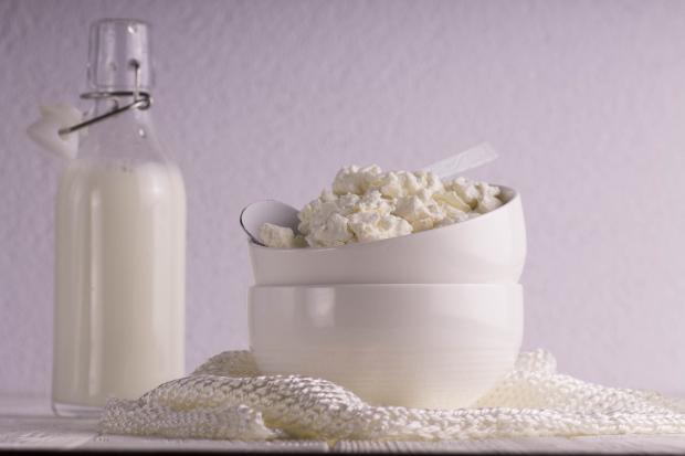Творог в белой мисочке и бутылка с молоком на столе