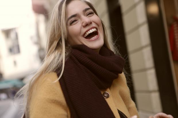 девушка в темном шарфе улыбается