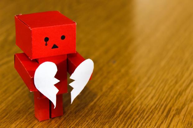 Бумажный робот с разбитым сердцем в руках
