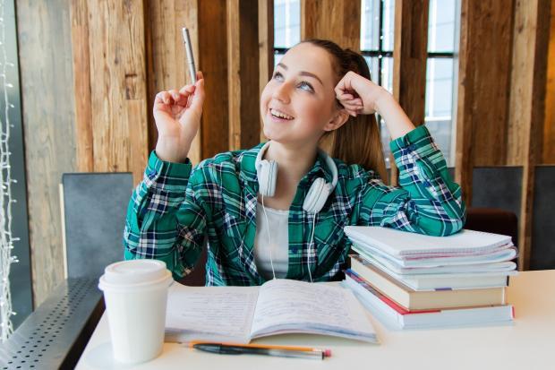 улыбающаяся девушка сидит перед стопкой учебников