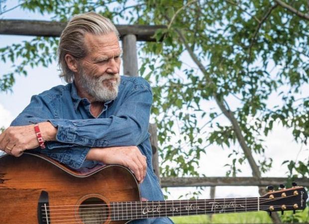 Джефф Бриджес в джинсовой рубашке и с гитарой в руках