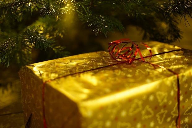 подарок под новогодней елкой в золоченой бумаге