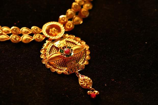 золотое колье с крупным медальоном на черном фоне