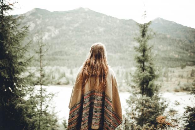 Светловолосая девушка в коричневом платке стоит в заснеженном лесу
