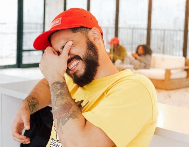 Молодой мужчина в желтой футболке и красной кепке смеется сидя на кресле