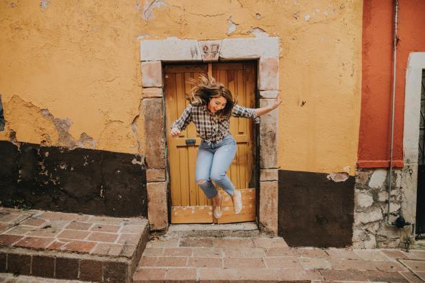 Девушка в джинсах подпрыгивает возле дома