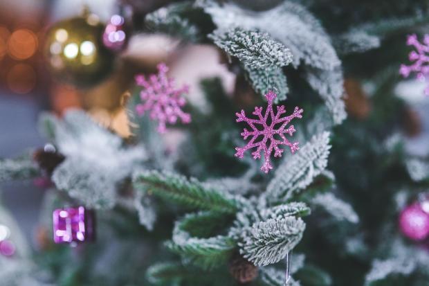 игрушки в виде снежинок висят на новогодней елке