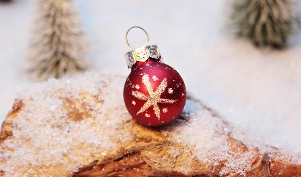красный елочный шар лежит на снегу