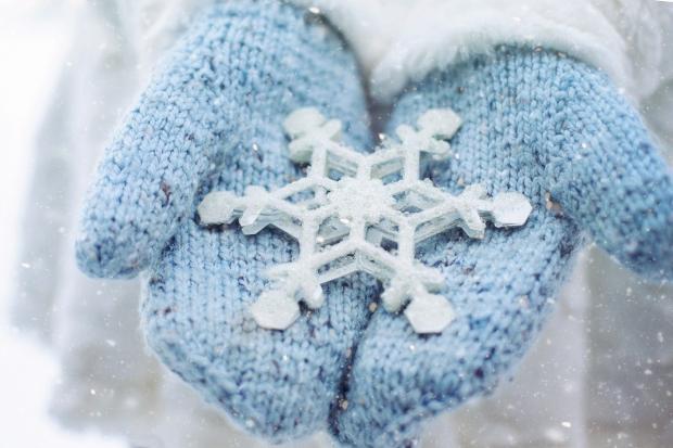 на голубых варежках лежит большая белая снежинка