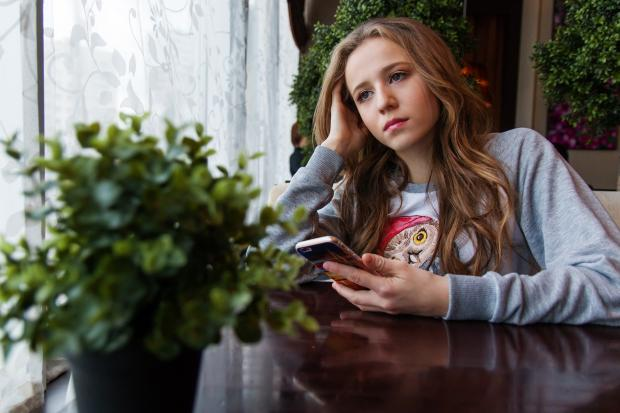 грустная девушка сидит за столиком в кафе