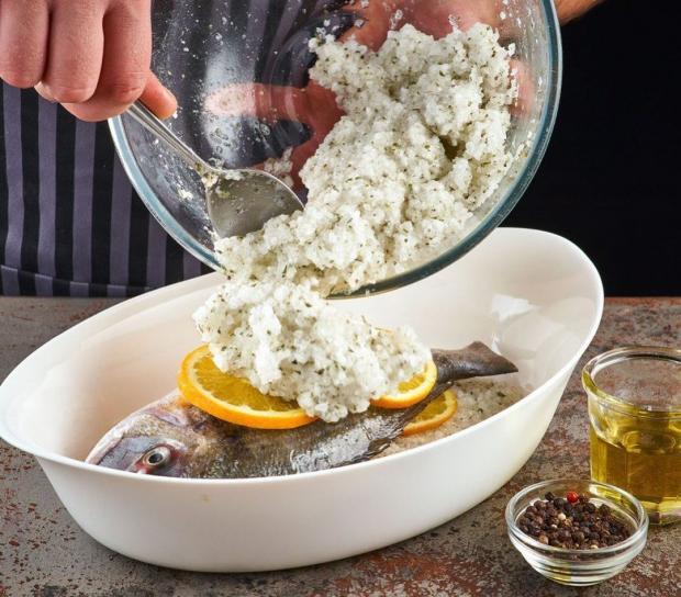 Повар засыпает рыбу солью