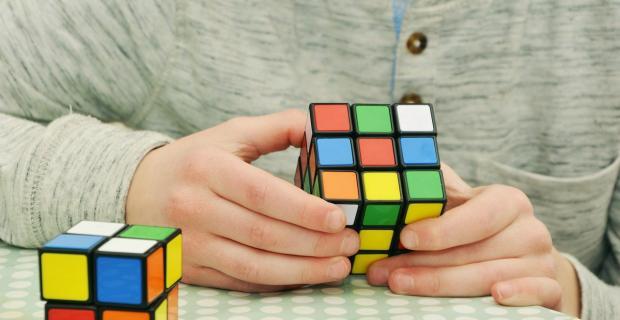 мужчина в светлом джемпере собирает кубик Рубика