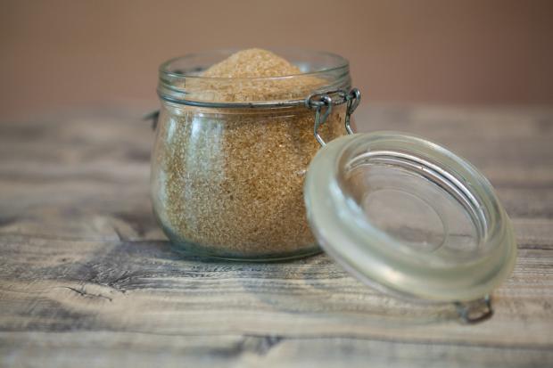 в стеклянную банку с откинутой крышкой насыпан коричневый сахар