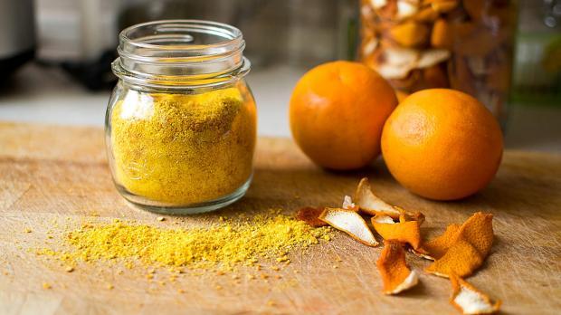 на столе стоят стеклянная баночка с порошком из апельсиновых корок и апельсины