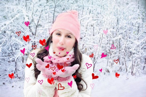 девушка в розовой шапке в заснеженном лесу
