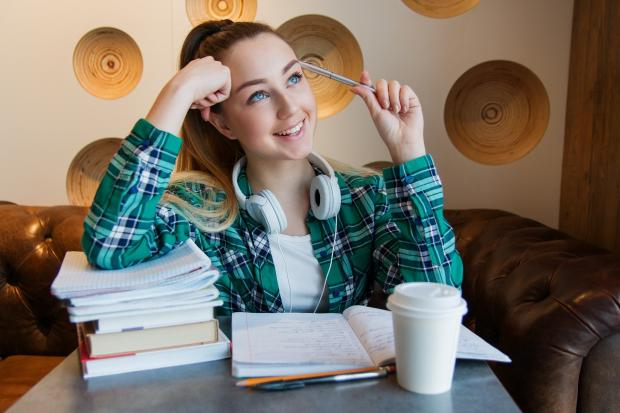 девушка сидит над учебниками задумчиво