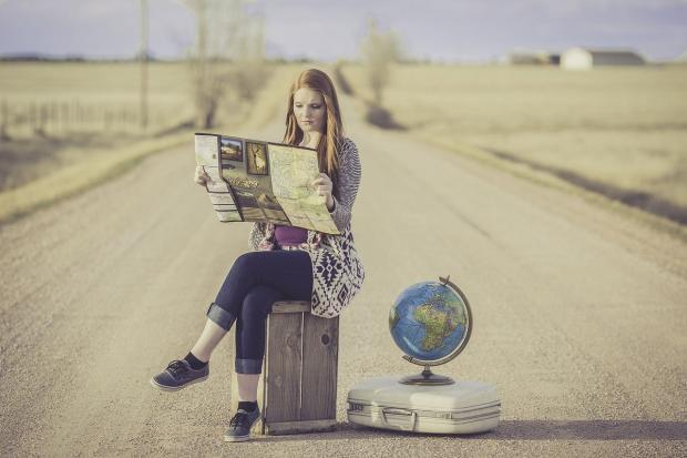 девушка сидит на шоссе с чемоданом и глобусом - путешествие