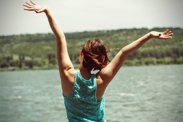 девушка с гипюровой майке салатного цвета подняла руки у летней реки