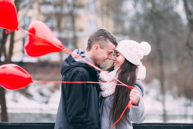 смеются мужчина и девушка с шарами в руках в виде сердца