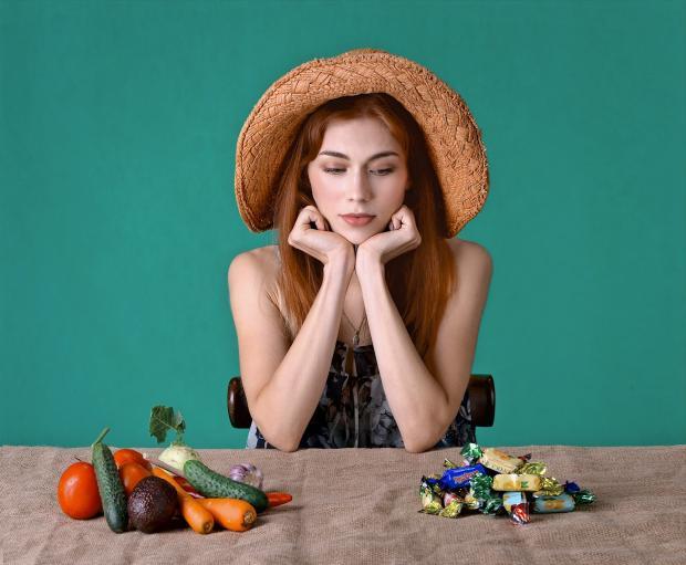 девушка в шляпке перед двумя  тарелками с конфетами и овощами
