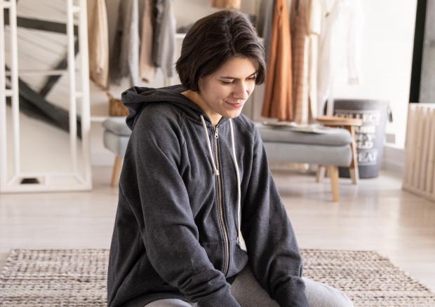 Девушка в серой кофте сидит на полу