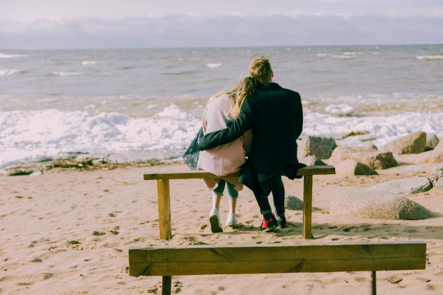Влюбленная пара на скамейке у моря