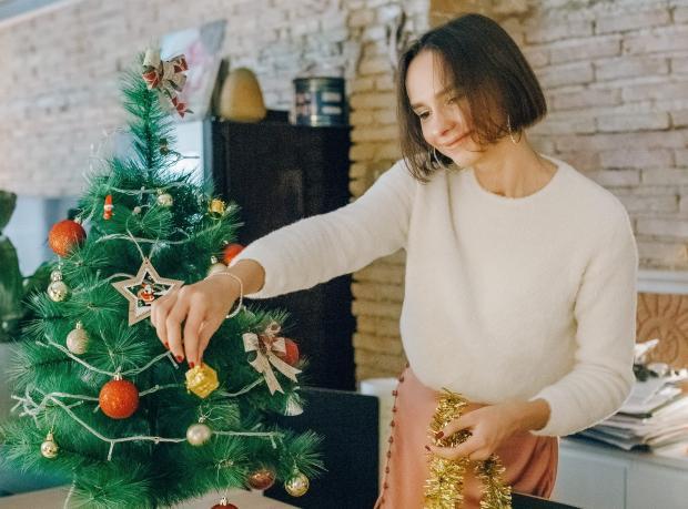 Девушка в белом свитере наряжает елку