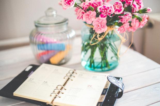 Блокнот и ваза с цветами на столе